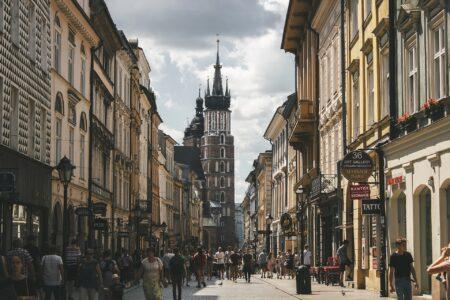 Zatłoczona ulica przy krakowskim rynku z widokiem na Kościół Mariacki