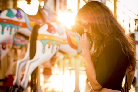 Kobieta stojąca przed karuzelą w parku rozrywkii